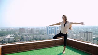 Yoga and meditation in a modern city. Young woman doing yoga on the roof. 20s. 1080p Slow Motion.