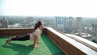 Yoga and meditation in a modern city. Young woman doing yoga on the roof. 20s. 4k