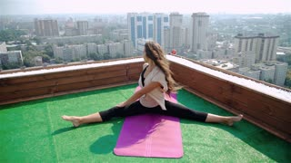 Yoga on rooftop. Happy young woman stretching on roof with city and mountains view. 20s. 1080p Slow Motion