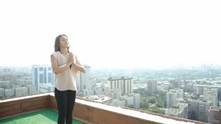 Yoga on rooftop. Happy young woman stretching on roof with city and mountains view. 20s. 4k