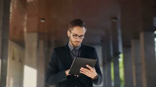 Young bearded businessman writting business e-mail using his tablet pc