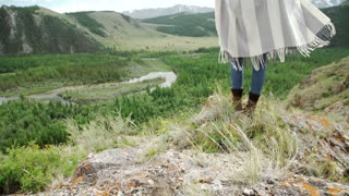 Young beautiful woman traveler wearing hat and poncho relaxing on the top of the hill with mountains and hills around