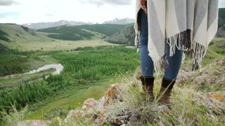 Young beautiful woman traveler wearing hat and poncho relaxing on the top of the hill with mountains and hills around.