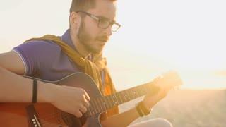 young boy plays guitar at sunset
