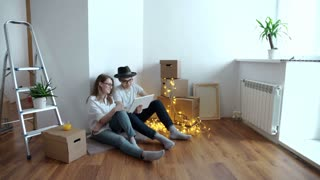 Young couple moving in new home. Sitting on floor and relaxing after cleaning and unpacking. Using tablet.