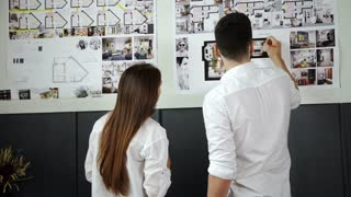 Young couple sitting on the floor and looking at the blueprint of new home 20s 4k.