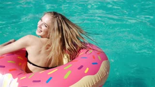 Young hipster millennial girl in sprinkled donut float at pool, festival, party, hotel, beach, event smiling with sunglasses. 20s. 1080p Slow Motion