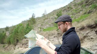 Young man reading a road map
