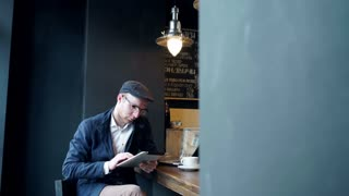 Young man using tablet computer in cafe