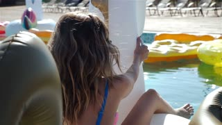 Young sexy woman 20s laying and relaxed near pool at summer holiday nice hot day. 1080p Slow Motion.