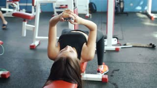 young sports woman using phone lying on the training apparatus in the gym 20s. 1080p Slow Motion
