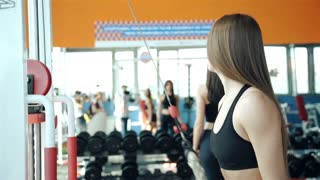 Young strong girl do exercises on cable crossover machine. 20s. 1080p Slow Motion