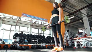 Young woman doing exercises on training apparatus in gym 20s. 1080p Slow Motion