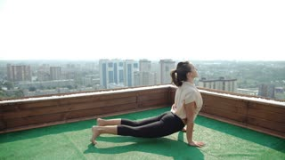 Young woman doing yoga on the mat on the roof. 20s. 4k