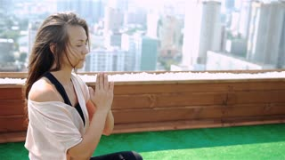 Young woman doing yoga on the mat on the roof, sitting in lotus posture. 20s. 1080p Slow Motion