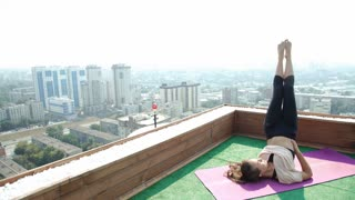 Young woman doing yoga on the mat on the roof, sitting in lotus posture. 20s. 4k