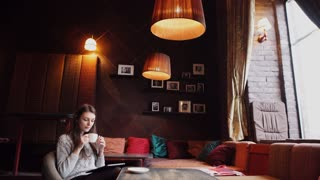 young woman drinking coffee and using tablet computer in a coffee shop