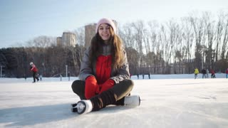 young woman fell down on skating rink and holding to her knee