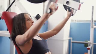 young woman flexing muscles on cable gym machine.