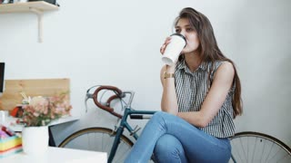 Young woman sipping coffee or tea and reading magazine