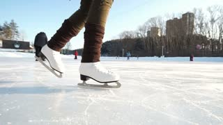 Young woman skating on ice with figure skates outdoors in the snow