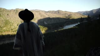 Young woman standing with backpack on cliff's edge and looking into