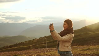 young woman traveler on a background of mountains takes photos on a mobile phone. Image with retro filter