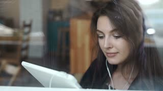 Young woman using tablet in coffee shop with headphone