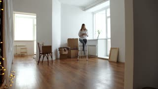 Young woman with phone sitting on wooden floor