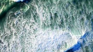 Aerial view looking down on ocean and waves break