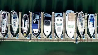 Aerial view looking straight down at boats docked by pier