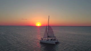 Aerial view of couple on sailboat at sunset