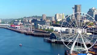 Aerial view of ferris wheel in front of Seattle skyline