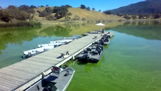 Aerial view of lakeside dock and boats by mountains on a sunny day 4