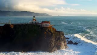Aerial view of lighthouse on cliff overlooking giant ocean waves under evening sky 2