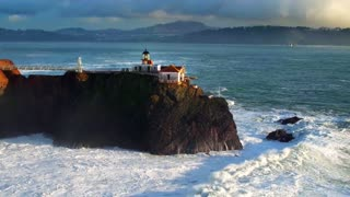 Aerial view of lighthouse on cliff overlooking giant ocean waves under evening sky 3