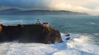 Aerial view of lighthouse on cliff overlooking giant ocean waves under evening sky 4