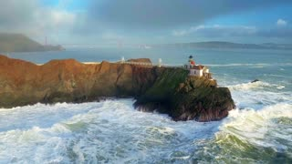 Aerial view of lighthouse on cliff overlooking giant ocean waves under evening sky 8