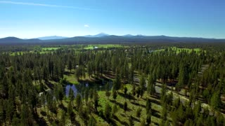 Aerial view of Oregon forest and stream by mountainside and blue sky 2