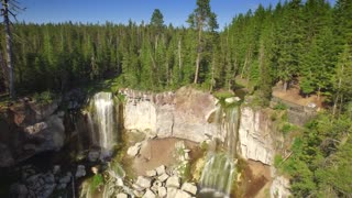 Aerial view of Oregon waterfall next to green trees and blue sky 3