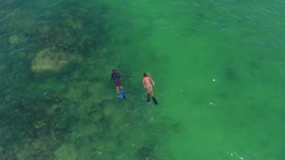 Aerial view of people snorkeling in clear ocean