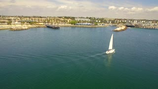 Aerial view of sailboat cruising by mainland under blue sky 2