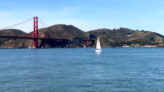 Aerial view of sailboat traveling by Golden Gate Bridge and mountains 2