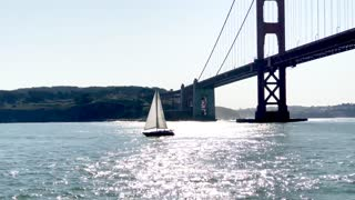 Aerial view of sailboat traveling by Golden Gate Bridge and mountains 3
