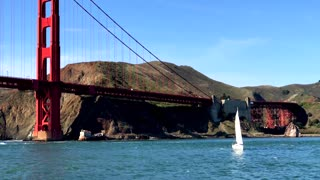 Aerial view of sailboat traveling by Golden Gate Bridge and mountains 4