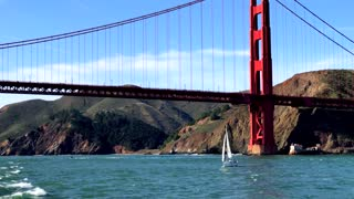 Aerial view of sailboat traveling by Golden Gate Bridge and mountains 5