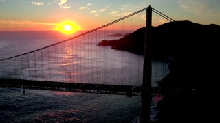 Aerial view of sunset behind San Francisco Bridge over water 2