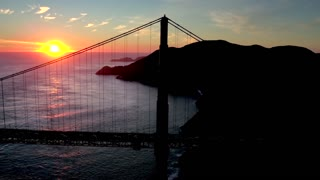 Aerial view of sunset behind San Francisco Bridge over water 3