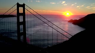 Aerial view of sunset behind San Francisco Bridge over water 4