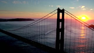 Aerial view of sunset behind San Francisco Bridge over water